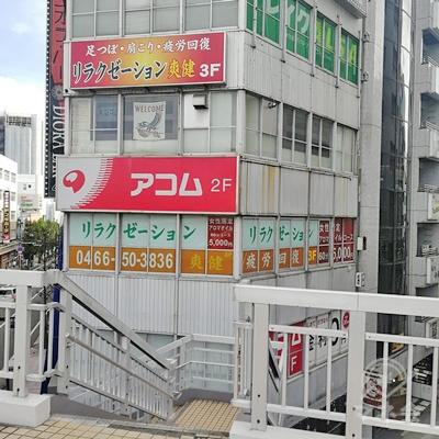 歩道橋を右に進み、建物の前にある階段を下りましょう。