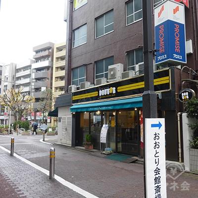 地上に下りて左手の茶色のビルに、プロミスの看板が見えます。ビル1階、ドトールコーヒーの角を曲がります。