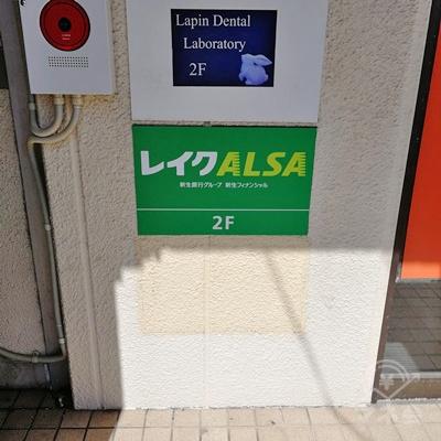 建物の奥にレイクALSAの看板が設置されています。レイクALSAは2階です。