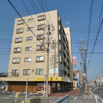 左手の7階建てのマンションの壁面に看板が見えてきます。