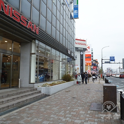 歩道の左に日産ディーラー、パチンコ店があります。