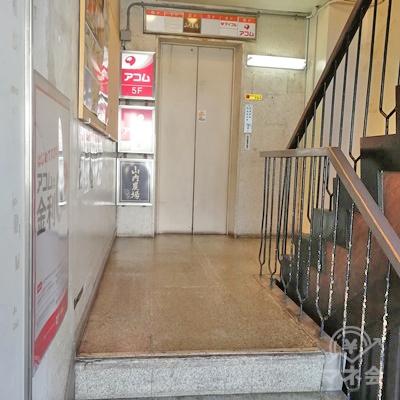 階段を上るとエレベーターがあります。アコムは5階です。