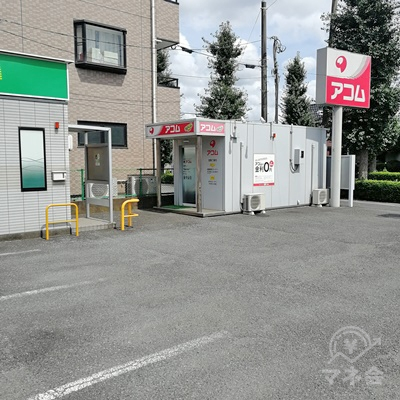 アコムの店舗と看板です。周りには駐車スペースがあります。