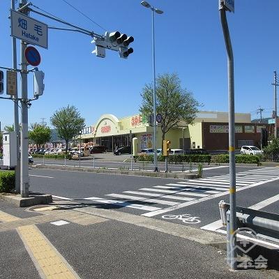 畑毛交差点で横断歩道を渡り、黄色の店舗方向へ進みます。