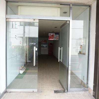 アコムの看板がかかっている下にビルの入口があります。