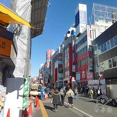 左手の商店街を進みます。アコムの大きな看板が見えます。