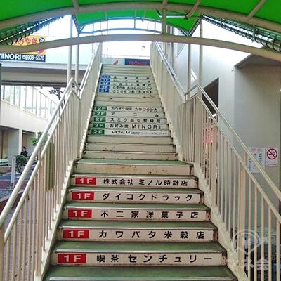 緑の屋根の屋外階段で2Fへ行きます。左横に案内板があります。