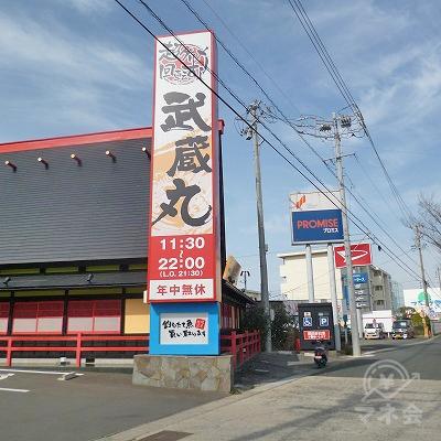 プロミスのポール看板手前に回転寿司の武蔵丸があります。