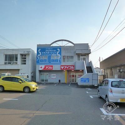 駐車場奥の2階建てビルの1階部分にアコムがあります。