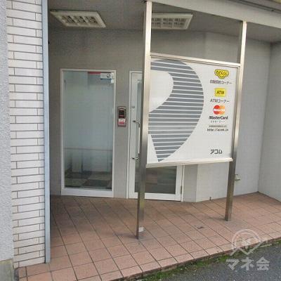アコムの店舗入口の様子です。入口の前には目隠しの化粧看板があります。