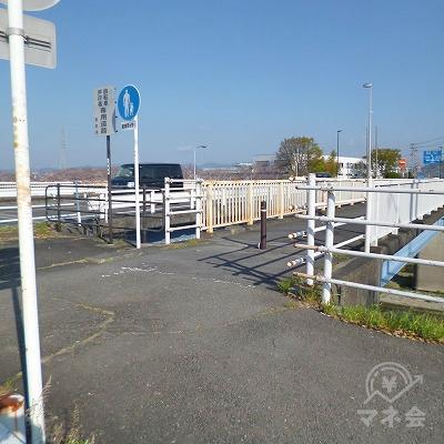 大通りとの交差点を右折して、橋で川を渡ってください。