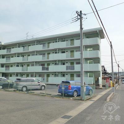 左手にペパーミントグリーン色のマンションが現れます。