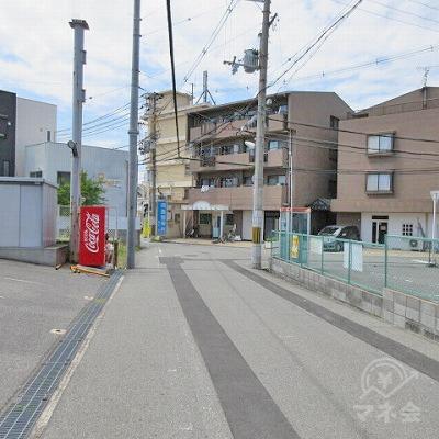 右に公衆電話。左に自動販売機。正面に青い看板(岡島整骨院)があります。