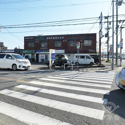 横断歩道の正面に栄和住建と書かれたレンガ仕上げの建物があります。