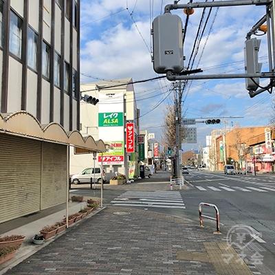 交差点左側のビルに看板が見えてきます。