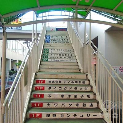 緑の屋根の屋外階段で2階に上がります。左横に案内板あります。