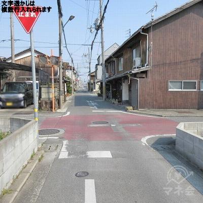 地面が赤っぽい十字路を直進します。