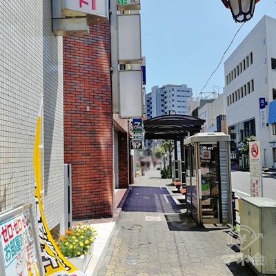 直進すると公衆電話やバス停があります。