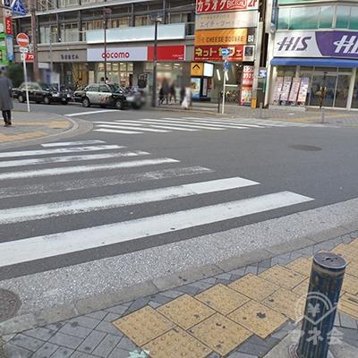 横断歩道を2つ渡って(左→正面)、ビル側に渡ります。