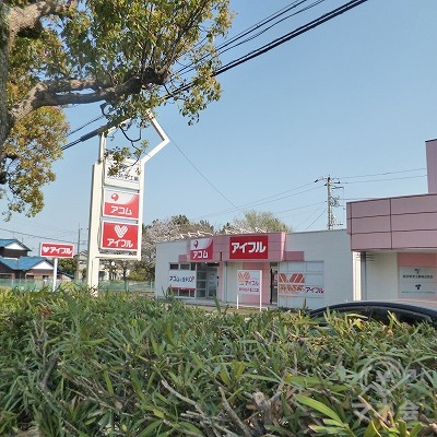 大通り沿いを500m東進すると、植栽の隙間からアイフルの看板と店舗が見えてきます。