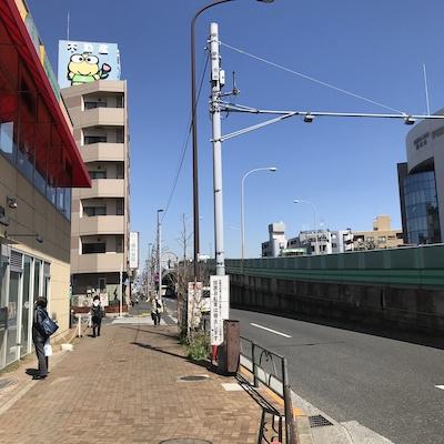 歩きはじめると右に立体交差、上に不動産屋のカエルの看板が見えます。