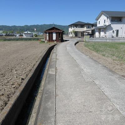 ここから左手の水路に沿って進み、正面の小屋を左へ進みます。