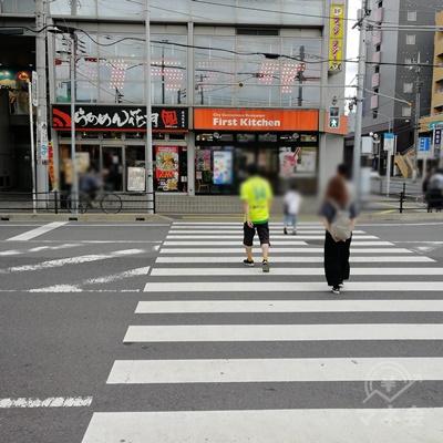 左の道を歩くと、信号があります。信号を渡り、左に曲がりましょう。