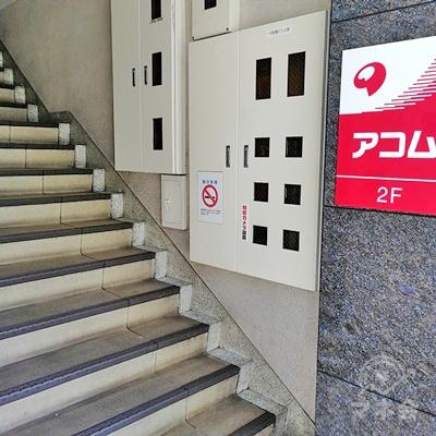 手前に階段があり、柱にアコムの看板があります。アコムは2階にあります。