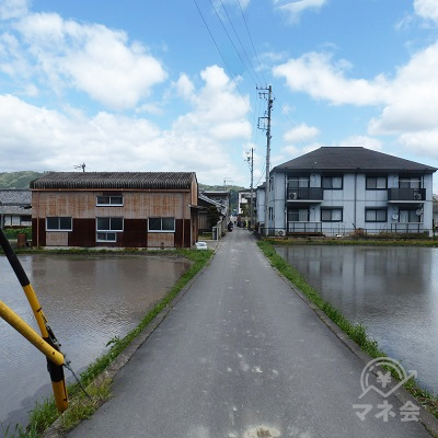 田んぼと家に囲まれた狭い道を直進します。