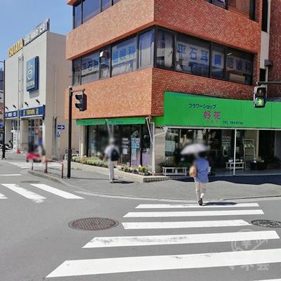左側にフラワーショップの緑の看板があります。信号を渡り左に行きます。