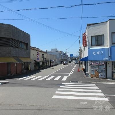 正面の青いビニール屋根の店舗を右に直進します。