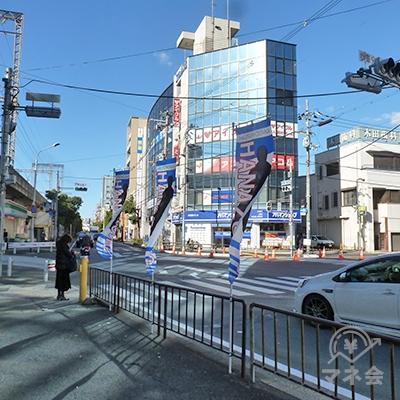 進むと交差点があり、対面のガラス張りのビルに店舗があります。
